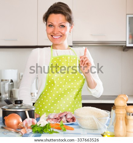Cheerful smiling housewife cooking meat with rice at domestic kitchen   - stock photo