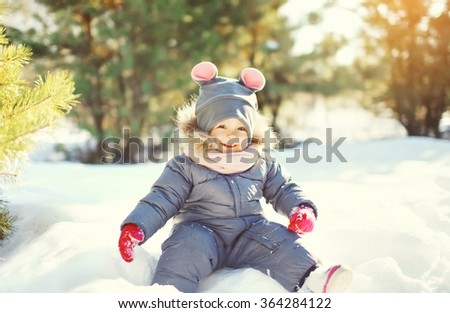 Cheerful smiling little child playing on snow in winter day - stock photo