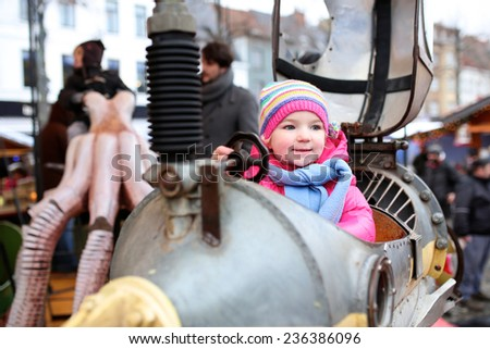 Cheerful smiling little child, toddler girl wearing colorful coat and knitted hat, having fun riding on the merry-go-round at christmas market festivities - stock photo