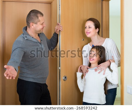 Cheerful smiling little girl and her mother visiting middle aged man indoors - stock photo