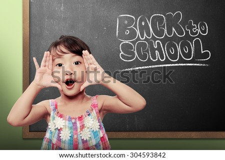 Cheerful smiling little girl on chalkboard background. Looking at camera. Back to school concept - stock photo