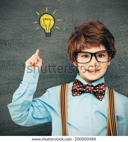 Cheerful smiling little kid (boy) against  chalkboard; raised his hand up. Looking at camera. School concept - stock photo