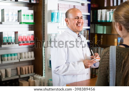 Cheerful smiling mature pharmacist serving young woman in pharmacy  - stock photo