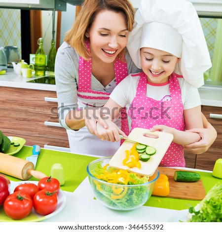 Cheerful smiling mother and daughter cooking a salad at the kitchen.