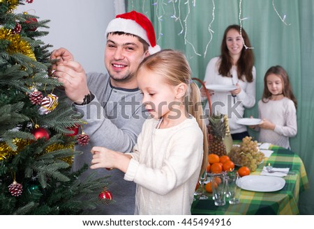 Cheerful smiling parents with two cute little daughters decorating Christmas tree and serving table. Focus on girl - stock photo