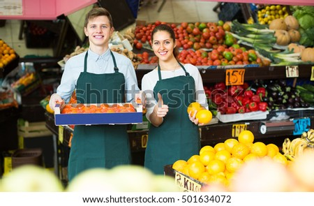 Cheerful smiling supermarket workers in fruit and vegetables section