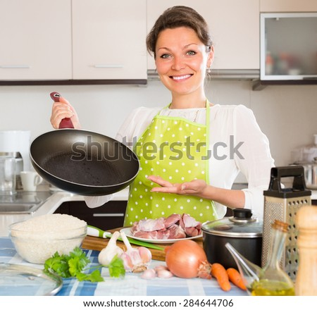 Cheerful smiling woman cooking meat with rice at home kitchen  - stock photo