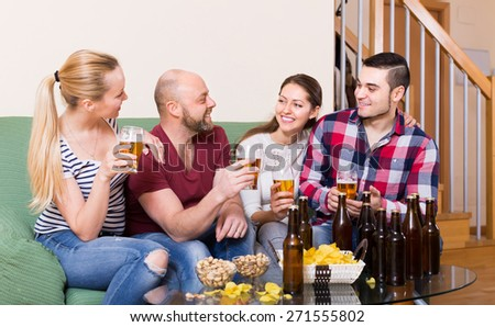 Cheerful smiling young adults drinking beer at home. Focus on man - stock photo