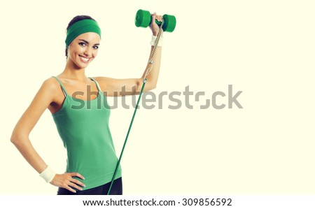 Cheerful smiling young brunette woman in green fitness wear exercising with dumbbell and growth, with blank copyspace area for slogan or text - stock photo
