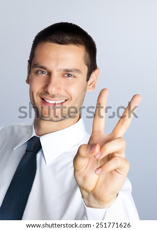 Cheerful smiling young businessman showing two fingers, or victory gesture, against grey background - stock photo