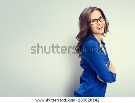 Cheerful smiling young businesswoman in glasses, with blank copyspace area for slogan or text - stock photo