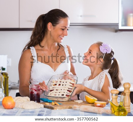 Cheerful smiling young housewife with daughter baking apple pie in kitchen