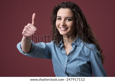 Cheerful smiling young woman thumbs up - stock photo