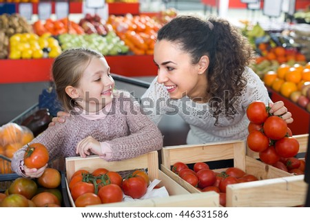 Cheerful smiling young woman with little daughter shopping globe tomatoes at  the market. Focus on woman