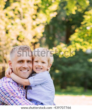Cheerful son giving a hug to his father in the park.