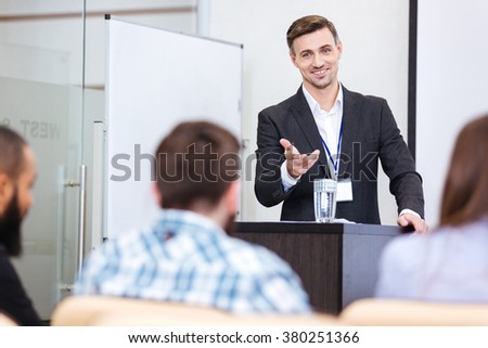 Cheerful speaker standing at the tribune in conference hall and pointing on male in audience  - stock photo