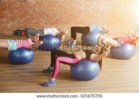 Cheerful sporty girls do sit ups - stock photo