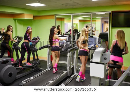 Cheerful sporty girls exercising in gym - stock photo