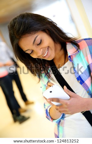 Cheerful student girl writing message on smartphone - stock photo
