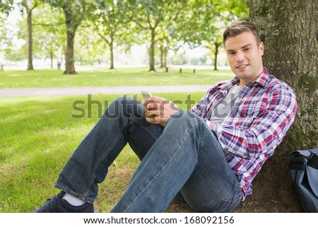 Cheerful student sending a text outside leaning on tree on college campus - stock photo
