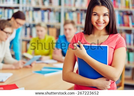 Cheerful student with copybook looking at camera in library - stock photo