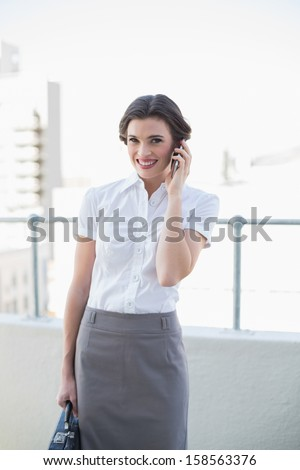 Cheerful stylish brown haired businesswoman making a phone call outdoors - stock photo