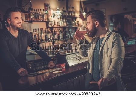 Cheerful stylish man drinking draft beer at bar counter in pub. - stock photo