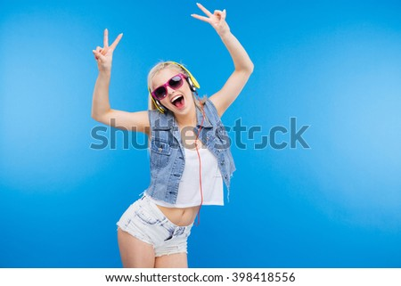 Cheerful stylish woman showing peace sign with fingers over blue background - stock photo