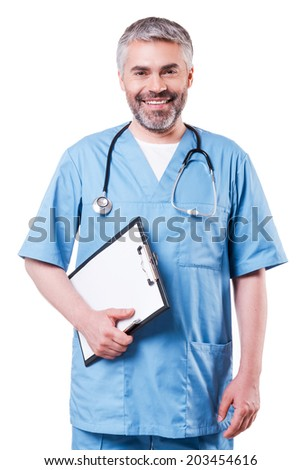 Cheerful surgeon. Cheerful mature doctor looking at camera and smiling while holding clipboard and standing isolated on white - stock photo