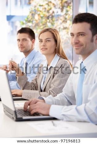 Cheerful team of young businesspeople listening presentation in meeting room.? - stock photo