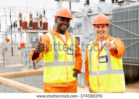 cheerful technicians giving thumbs up in substation - stock photo