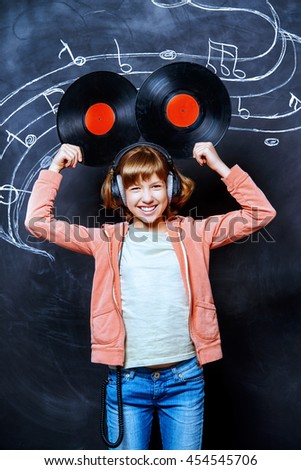 Cheerful teen girl enjoys the music. Generation. Studio shot. - stock photo