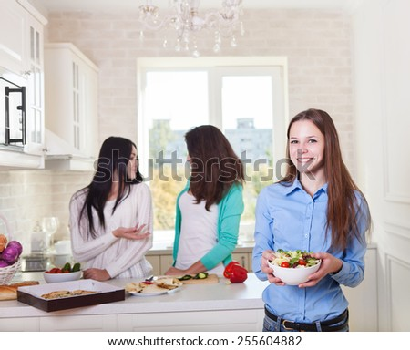 Cheerful teen girls preparing salad together in the kitchen - stock photo