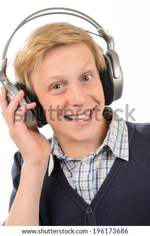 Cheerful teenage boy listening to music through headphones white background - stock photo