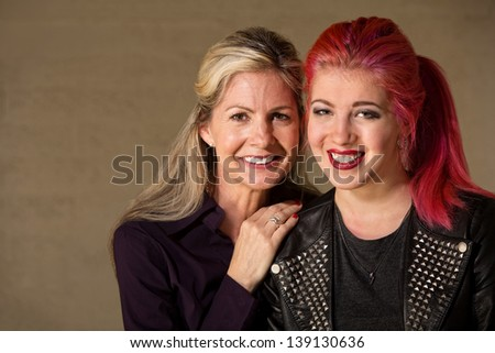 Cheerful teenage female with blond mother indoors - stock photo