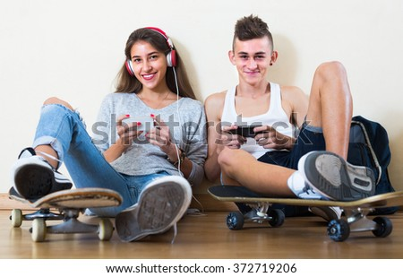 Cheerful teenage friends sitting on floor and relaxing with mobile phones 