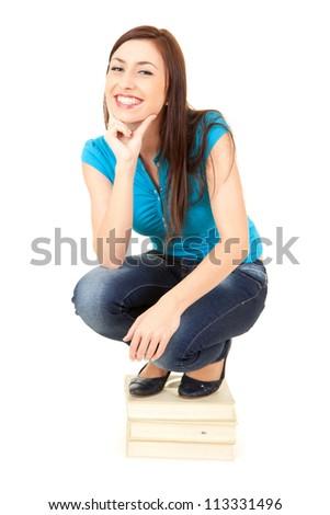 cheerful teenage girl crouching on stack of books, white background - stock photo
