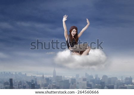 Cheerful teenage girl expressing her success while sitting on the cloud and using laptop at the sky - stock photo