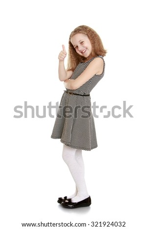 Cheerful teenage girl in a gray silk dress tied with a black belt shows hand gesture everything is OK-Isolated on white background - stock photo