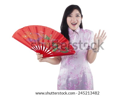 Cheerful teenage girl with surprised expression while wearing traditional clothes and holding a fan