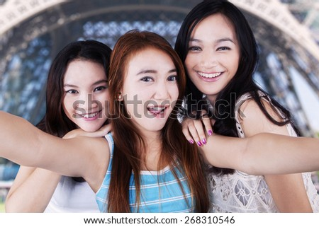 Cheerful teenage girls enjoy holiday in Paris and take a selfie picture near the Eiffel Tower - stock photo