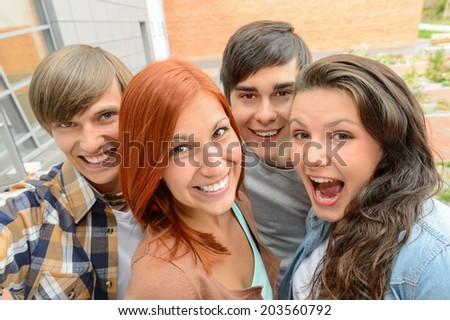 Cheerful teenager friends taking selfie having fun outside campus - stock photo