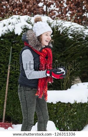 Cheerful teenager girl in winter cloths making a snowball