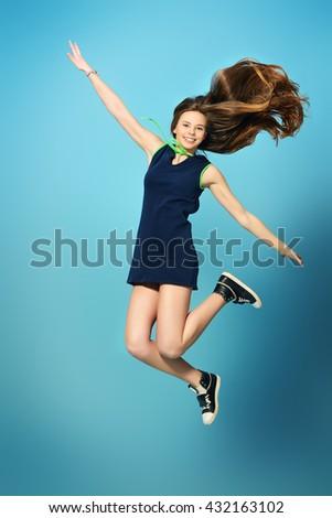 Cheerful teenager girl jumping for joy. - stock photo