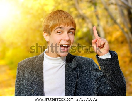 Cheerful Teenager with Finger Up in the Autumn Park - stock photo