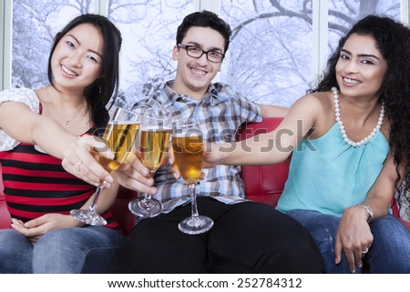 Cheerful teenagers enjoy togetherness by drinking beer in winter day
