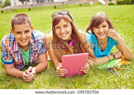 Cheerful teenagers looking at camera during summer rest - stock photo