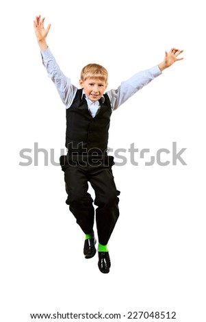 Cheerful ten years schoolboy jumping for joy. Isolated over white. - stock photo