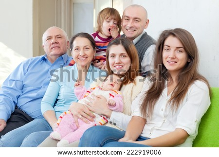 cheerful three generations family sits on sofa in home interior - stock photo