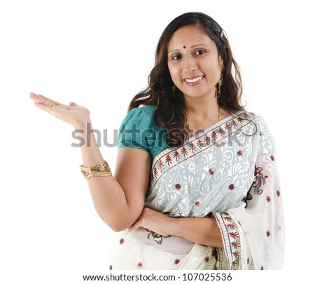 Cheerful traditional Asian Indian woman arm out showing empty space, isolated on white